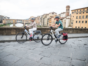 Two people riding their eBikes through the Toscana
