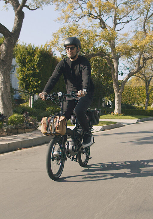 A Tern Vektron electric bicycle with the Bosch Active Line Plus motor is ridden down a tree-lined street in Los Angeles, California.