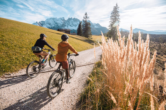 Two eBikers are taking a tour in sustainable vacations, in the background you can see the Dolomites in South Tyrol