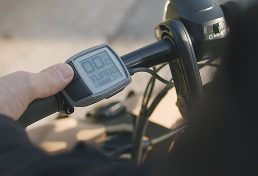 A detailed view of the Bosch Purion computer display is shown on the handlebar of a Tern electric bicycle.
