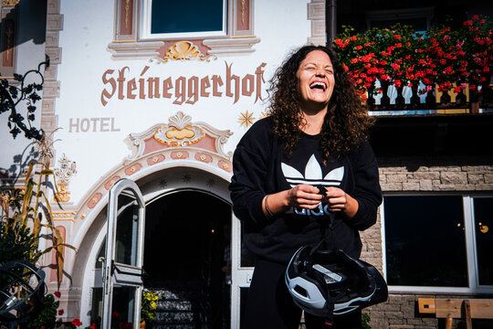 An eBiker stands in front of the Bio- und Bikehotel Steineggerhof, smiling and holding her helmet in her hand.