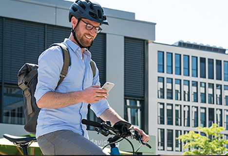 An eBiker looks, smiling, at his mobile phone